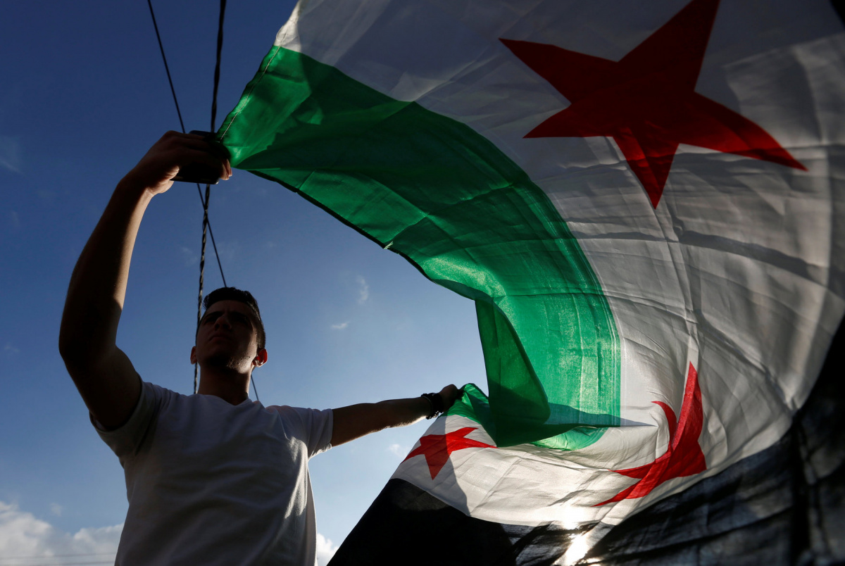A protester holds a Syrian opposition flag during a sit-in, in solidarity with the people of Aleppo against the Syrian regime, in front of the UNDP office in Amman, Jordan, December 17, 2016. REUTERS/Muhammad Hamed