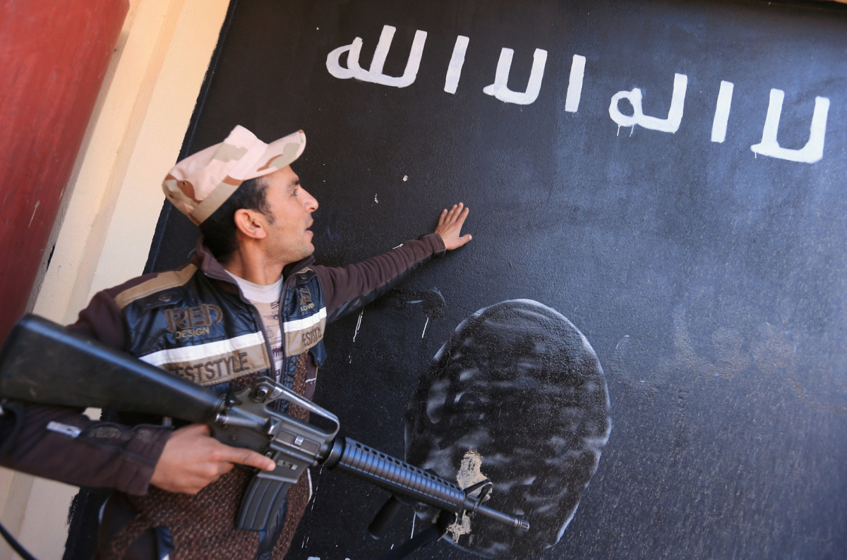 An Iraqi soldier looks at a wall painted in the colours of the black flag commonly used by Islamic State militants, in the village of Argoob, Iraq, January 6, 2017. REUTERS/Ari Jalal