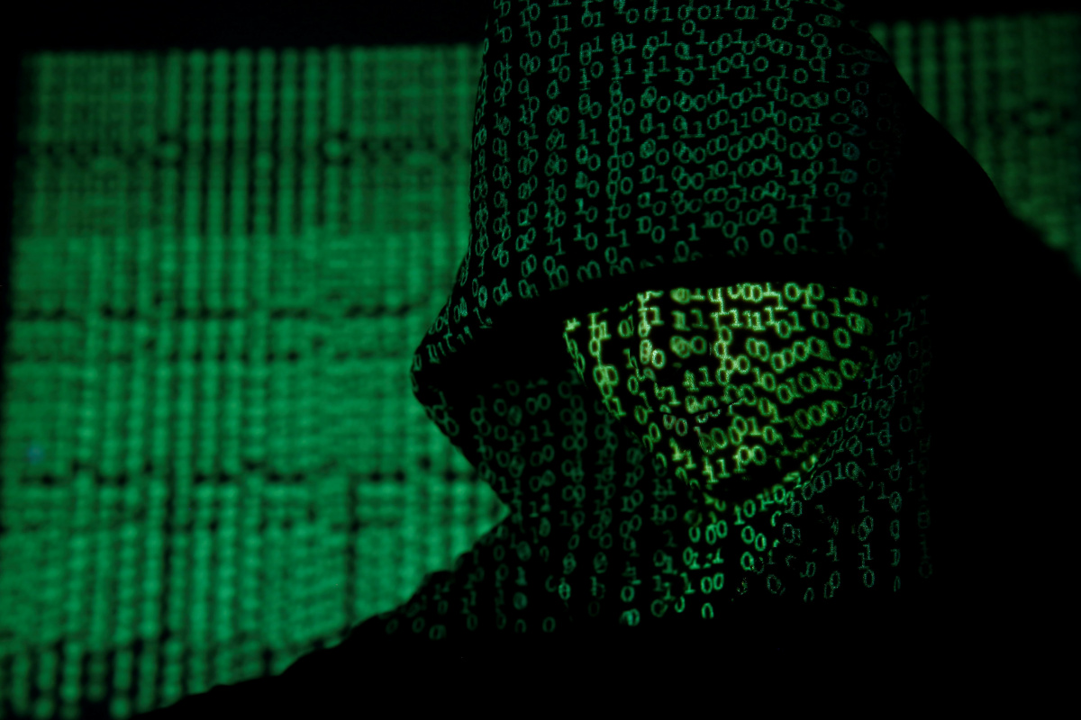 A projection of cyber code on a hooded man is pictured in this illustration picture taken on May 13, 2017. Capitalizing on spying tools believed to have been developed by the U.S. National Security Agency, hackers staged a cyber assault with a self-spreading malware that has infected tens of thousands of computers in nearly 100 countries. REUTERS/Kacper Pempel/Illustration