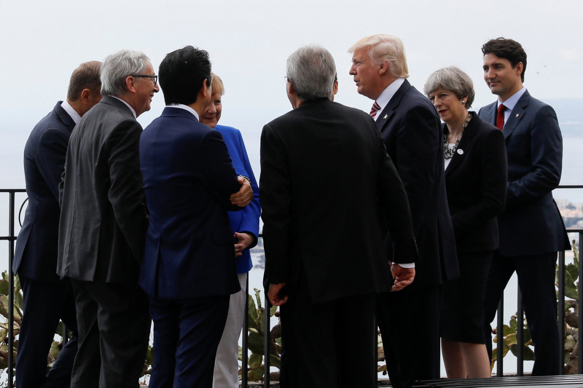 From L-R, European Council President Donald Tusk, European Commission President Jean-Claude Juncker, Japanese Prime Minister Shinzo Abe, German Chancellor Angela Merkel, Italian Prime Minister Paolo Gentiloni, U.S. President Donald Trump, French President Emmanuel Macron (hidden), Canadian Prime Minister Justin Trudeau and Britain's Prime Minister Theresa May gather as they attend the G7 Summit in Taormina, Sicily, Italy, May 26, 2017. REUTERS/Jonathan Ernst