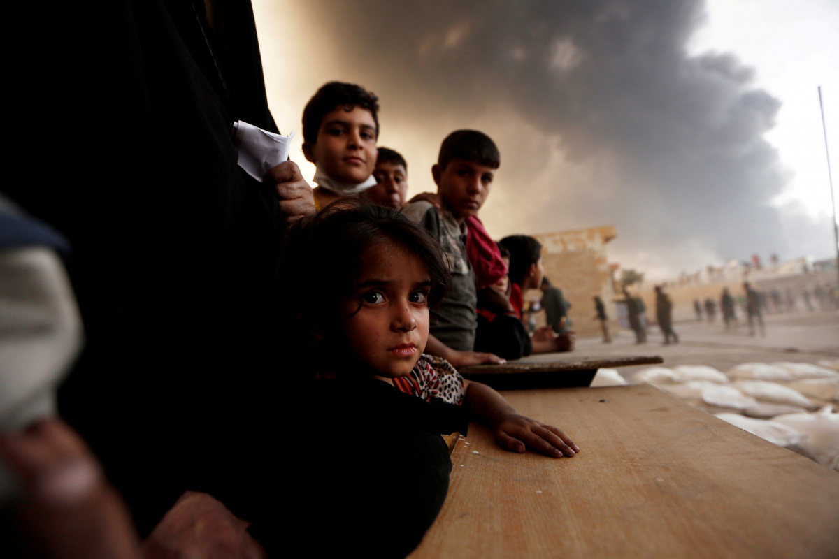 Newly displaced people wait to receive food supplies at a processing center for displaced people in Qayyara, south of Mosul, Iraq, October 21, 2016. REUTERS/Zohra Bensemra