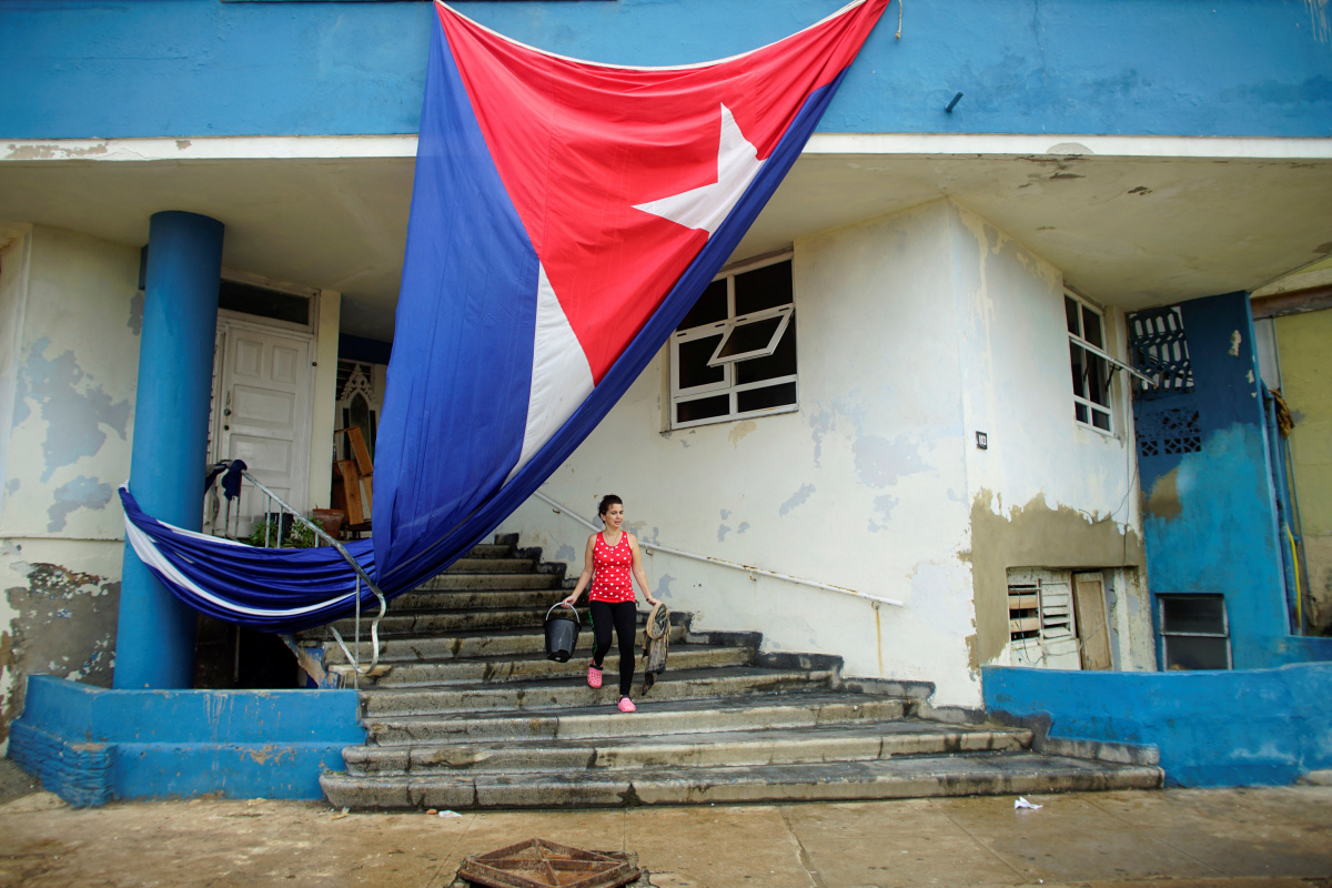 A woman cleans the entrance of a building next to a Cuban flag hung up to dry after Hurricane Irma caused flooding and a blackout, in Havana, Cuba September 11, 2017. REUTERS/Alexandre Meneghini