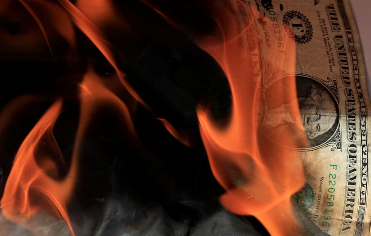 Supporters of Kenyan opposition leader Raila Odinga of the National Super Alliance (NASA) coalition burn a U.S. dollar bill during a protest against U.S. Ambassador Robert Godec near the embassy building in Gigiri area of Nairobi, Kenya February 16, 2018. REUTERS/Thomas Mukoya