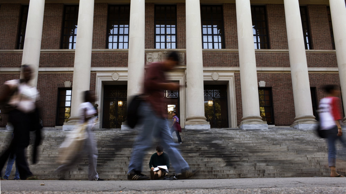 A students sits on the steps of Widener Library at Harvard University in Cambridge, Massachusetts