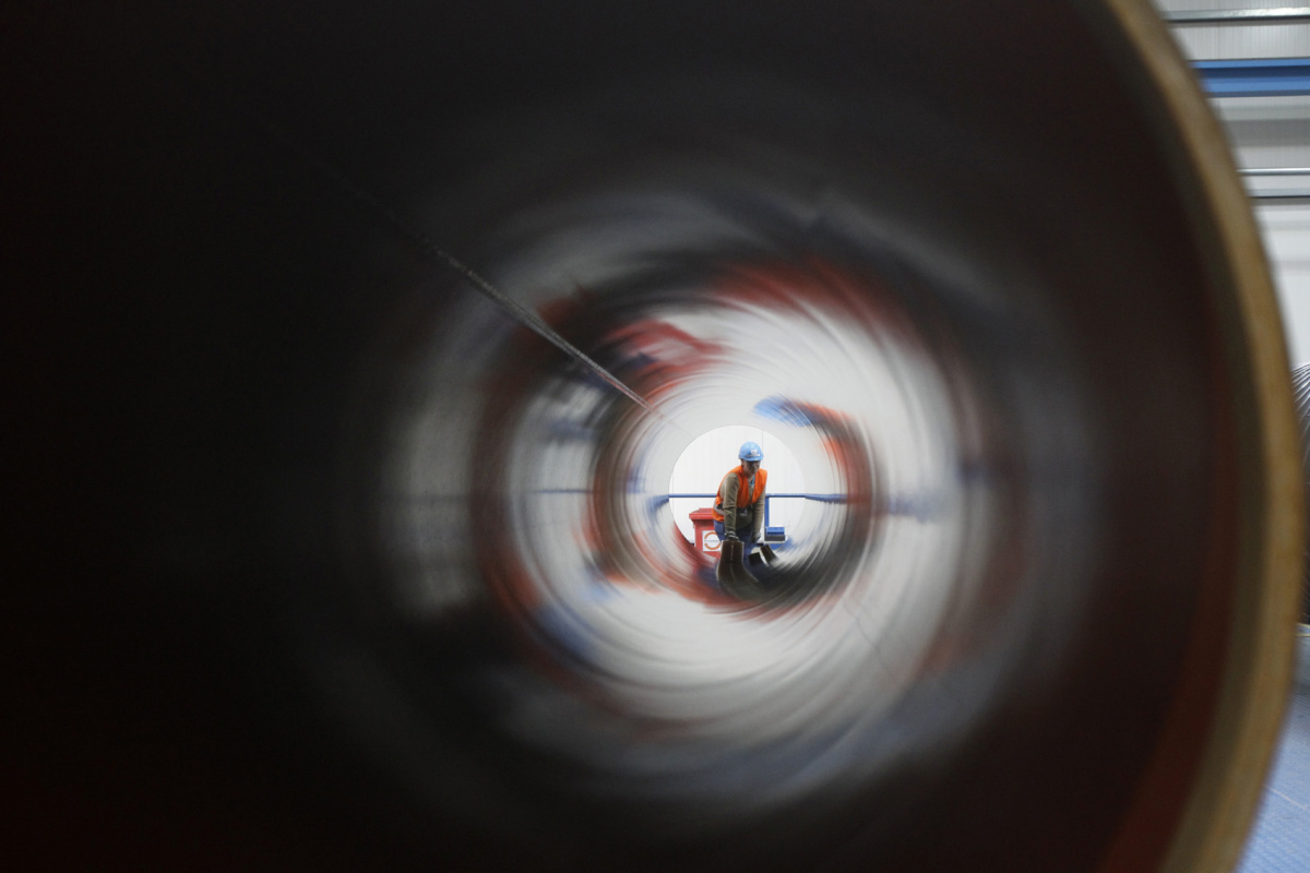 A worker is seen through a pipe at French pipe coating company EUPEC in Sassnitz May 6, 2011. EUPEC is working to complete around 200,000 pipes for Nord Stream, which is building two 1,220km-long roughly parallel gas pipelines across the Baltic Sea from Russia to Germany with an overall annual capacity of 55 billion cubic metres (bcm). REUTERS/Tobias Schwarz