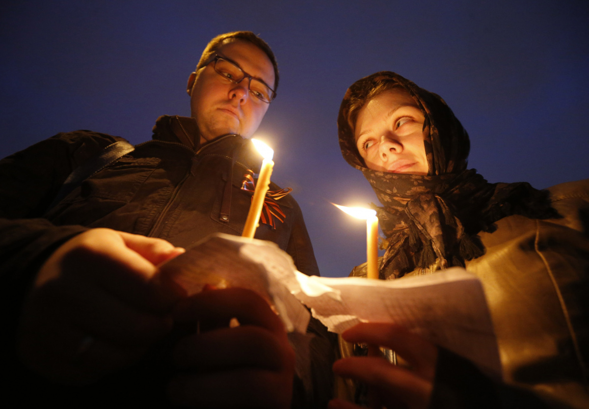 People hold lit candles during a rally organized by supporters of the self-proclaimed republics of Donbass and Luhansk to commemorate victims of the military conflict in the eastern regions of Ukraine