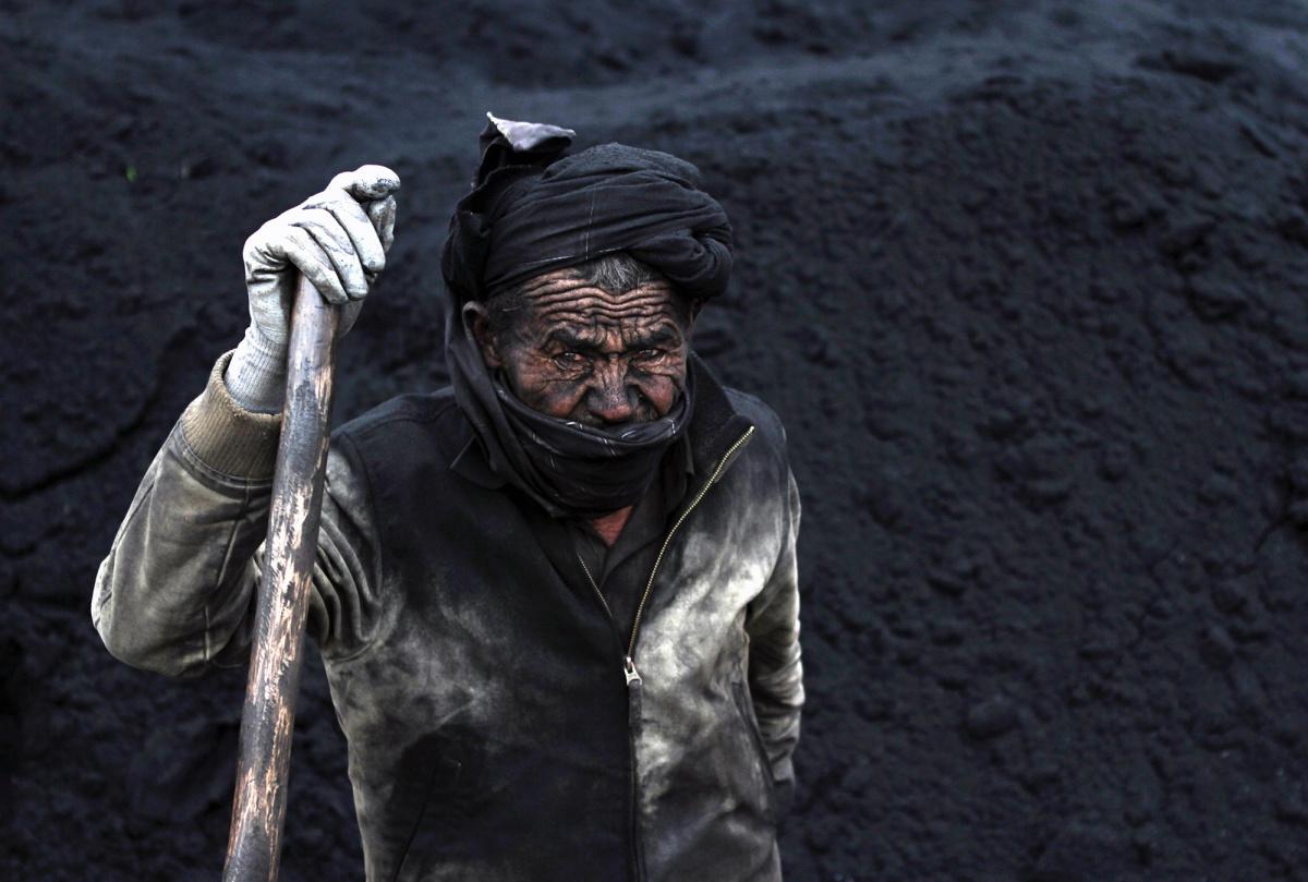 A labourer takes a break at a coal dump site outside Mazar-i-Sharif, November 6, 2014. Picture taken on November 6, 2014. REUTERS/Anil Usyan.