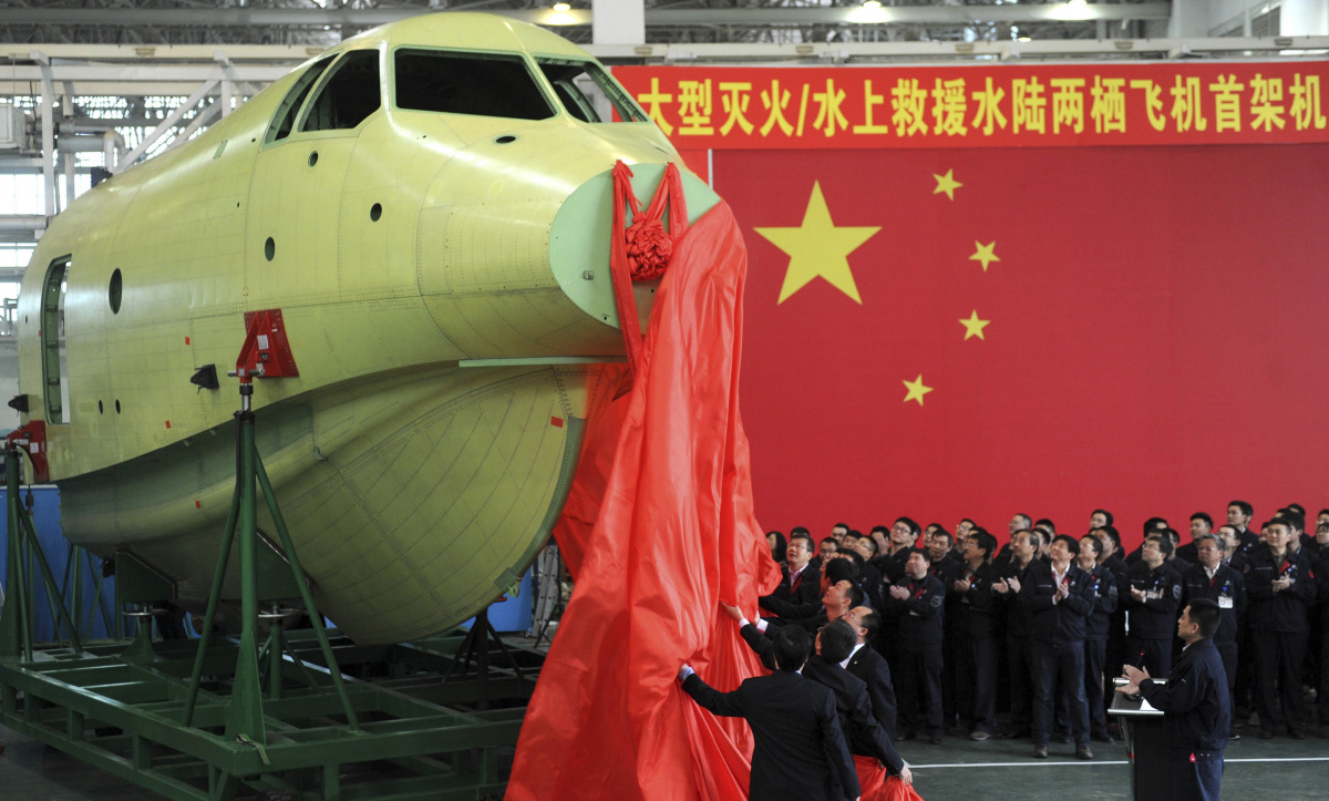 Officials of Aviation Industry Corporation of China (AVIC) unveil the newly-made nose of amphibious aircraft AG600, during a ceremony at a factory in Chengdu, Sichuan province
