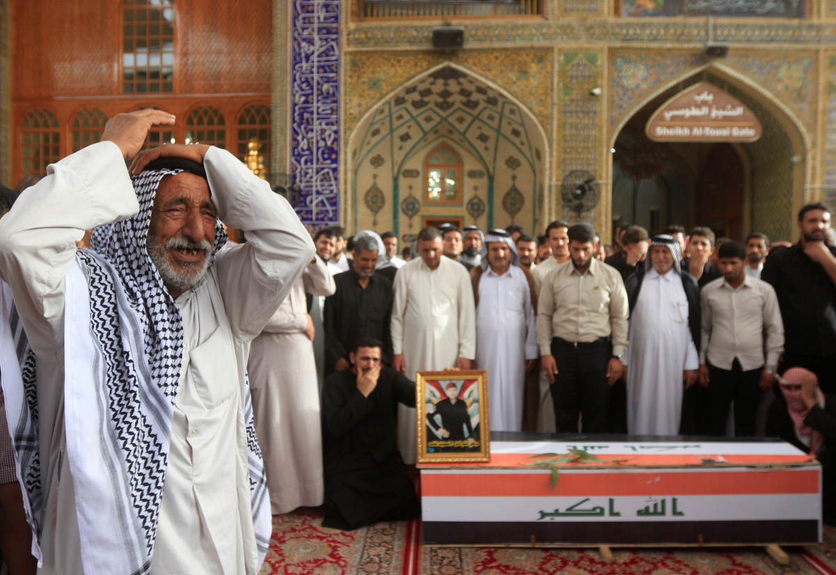 A man reacts near the coffin of a member of Iraqi security forces, who was killed during clashes in Mosul, at his funeral in Najaf, Iraq June 22, 2017. REUTERS/Alaa Al-Marjani