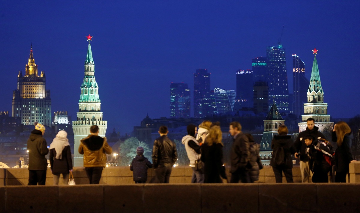 """People stand on the Great Moskvoretsky Bridge, with the headquarters of Russian Foreign Ministry, the Kremlin towers and the Moscow International Business Center also known as """"Moskva-City"""", seen in the background, in central Moscow, Russia"""