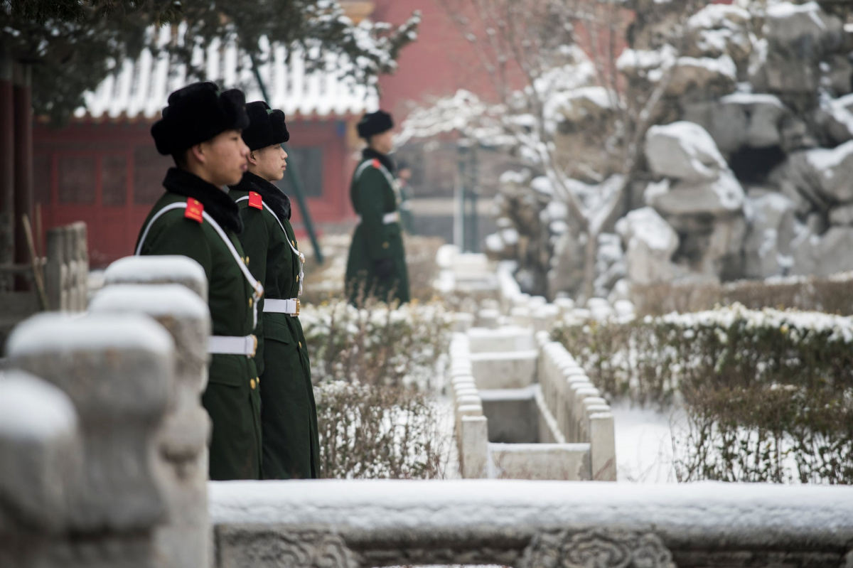 Chinese paramilitary guards stand in the snow at the Forbidden City in Beijing