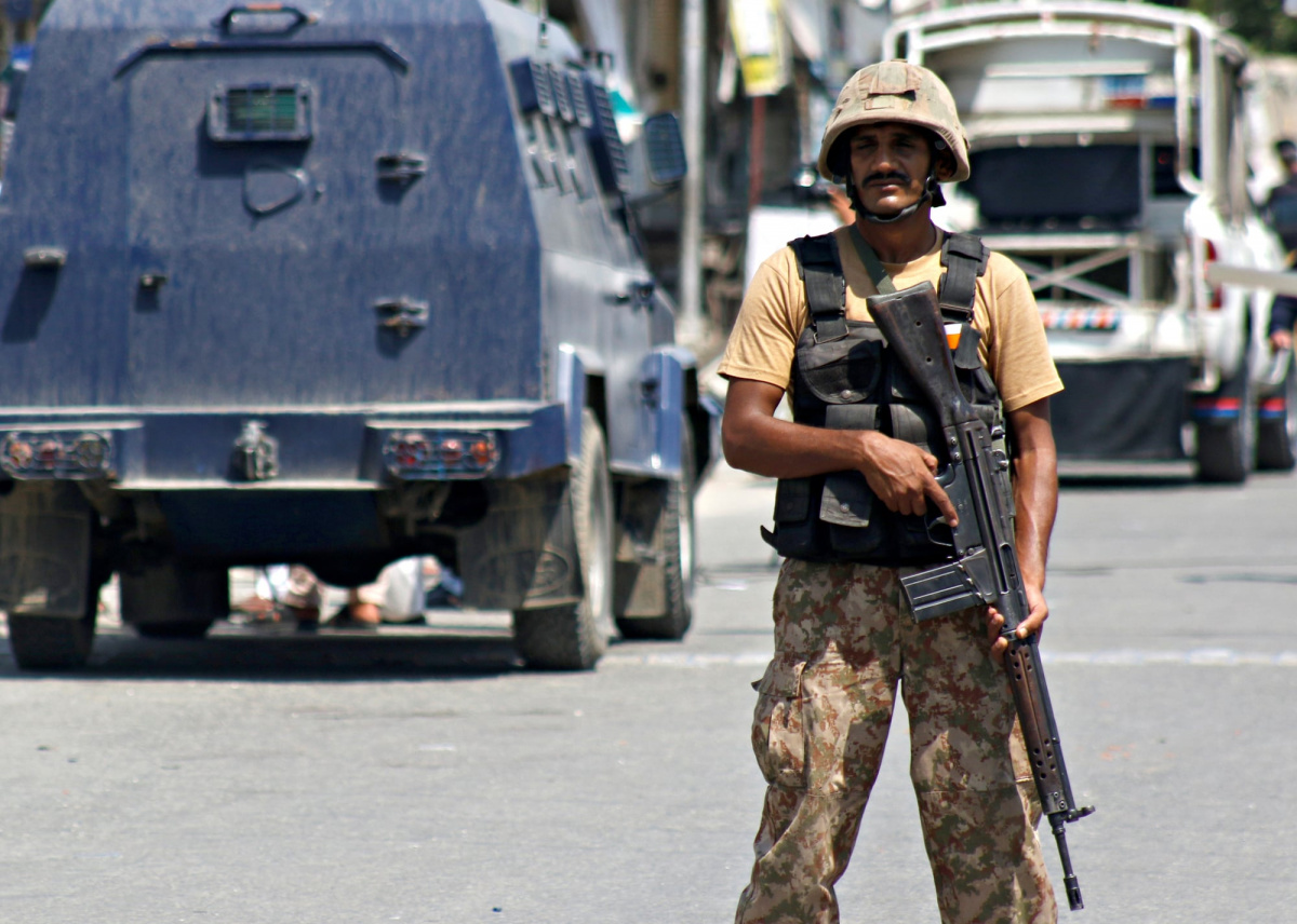 An army soldier stands guard on a road, after twin bomb attack occurred at a court, in Mardan, Pakistan