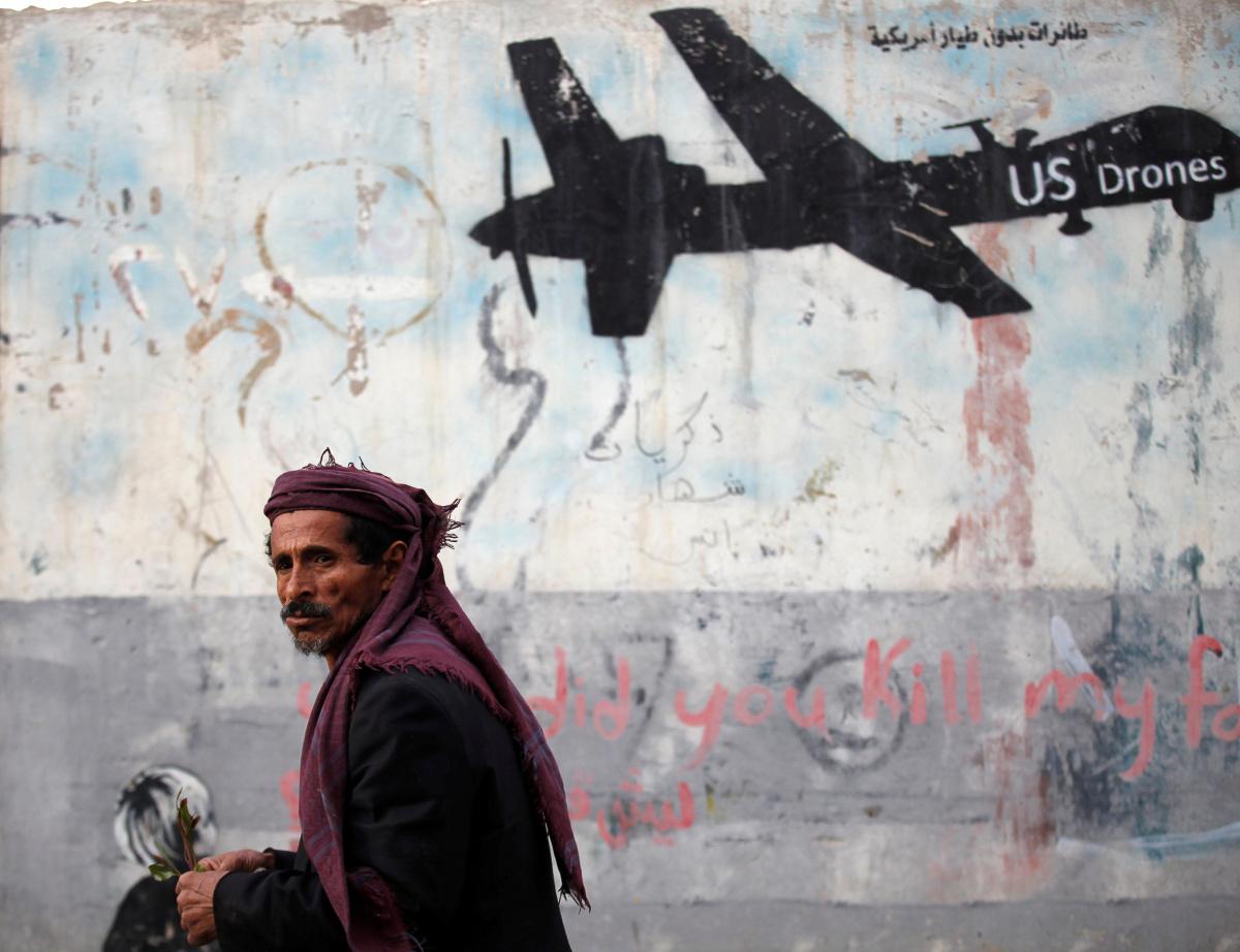A man walks past a graffiti, denouncing strikes by U.S. drones in Yemen, painted on a wall in Sanaa, Yemen