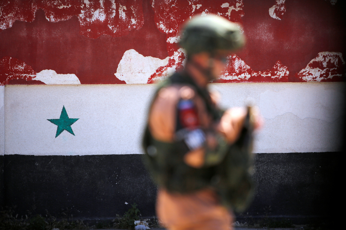 A Russian soldier stands guard near a Syrian national flag drawn on the wall as rebel fighters and their families evacuate the besieged Waer district in the central Syrian city of Homs, after an agreement reached between rebels and Syria's army, Syria May 21, 2017.