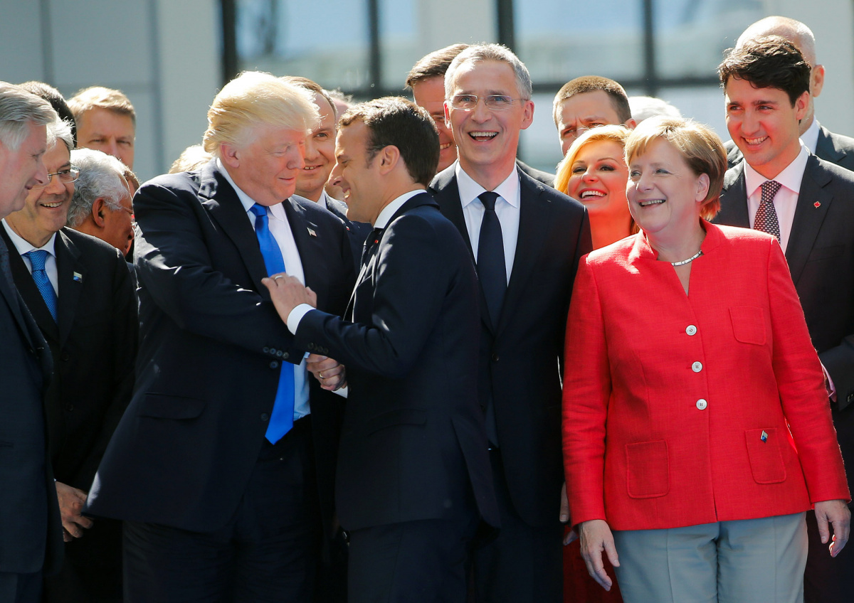 U.S. President Donald Trump jokes with French President Emmanuel Macron about their shake hands in front of NATO leaders, including Canada's Prime Minister Justin Trudeau (R), German Chancellor Angela Merkel and NATO Secretary General Jens Stoltenberg (3rdR), Belgium King Philippe (L) and Italian Prime Minister Paolo Gentiloni, at the start of the NATO summit at their new headquarters in Brussels, Belgium, May 25, 2017. REUTERS/Jonathan Ernst