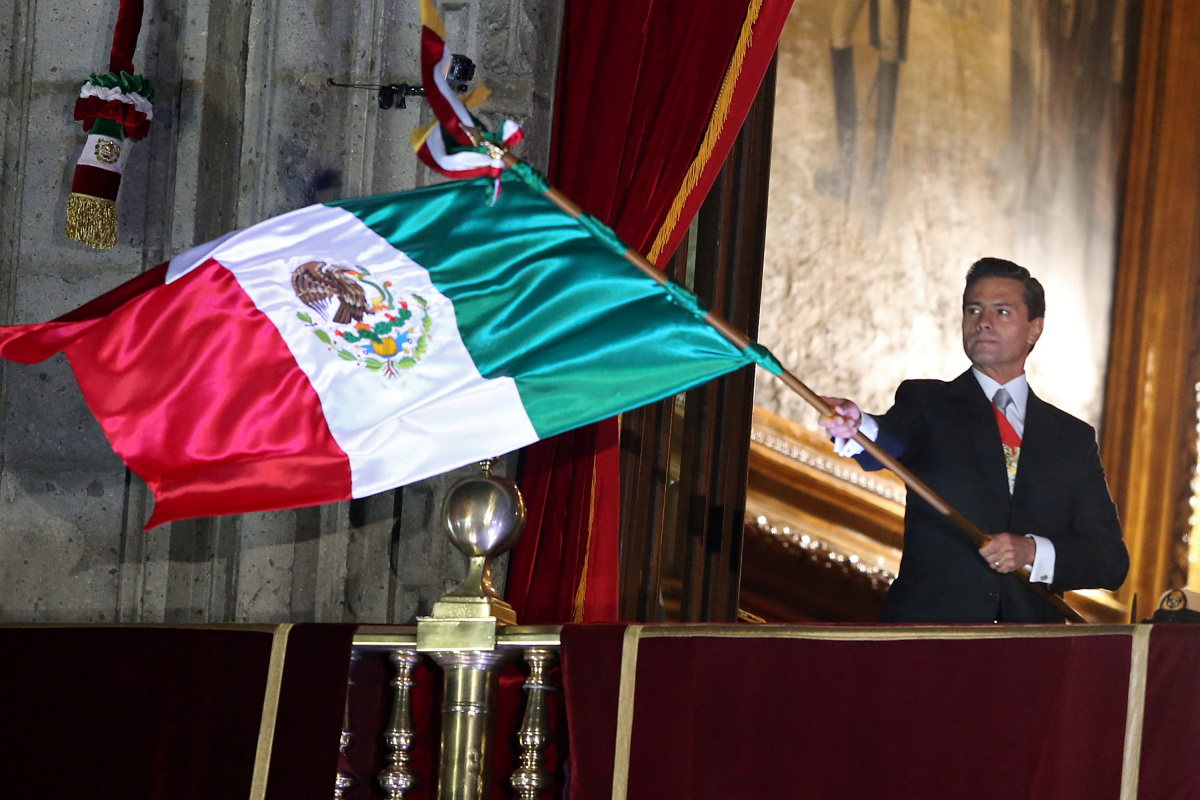 """Mexico's President Enrique Pena Nieto waves the national flag after he shouted the """"Cry of Independence"""", as Mexico marks the 207th anniversary of the day rebel priest Miguel Hidalgo set it on the path to independence, in Mexico City, Mexico, September 15, 2017. REUTERS/Edgard Garrido"""