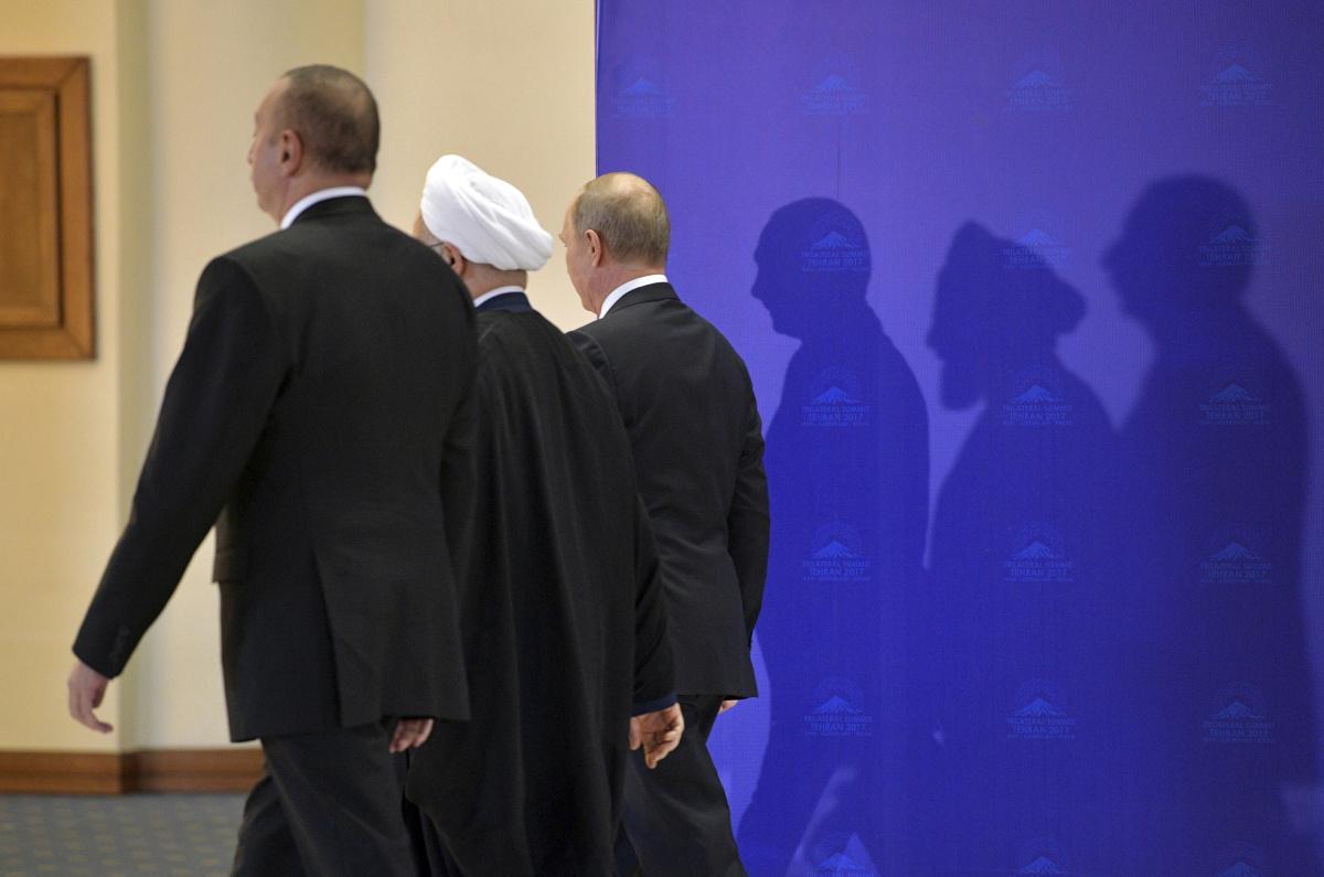 (R-L) Russia's President Vladimir Putin, Iran's President Hassan Rouhani and Azerbaijan's President Ilham Aliyev walk during a meeting in Tehran, Iran
