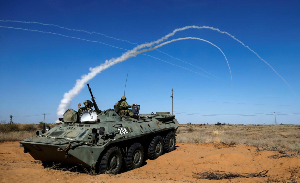 Os militares russos descansam sobre um transportador de pessoal blindado (APC), já que os sistemas de mísseis de defesa aérea S-300 lançam mísseis durante a competição Keys to the Sky nos Jogos Internacionais do Exército 2017 no campo de tiro Ashuluk fora de Astrakhan, Rússia