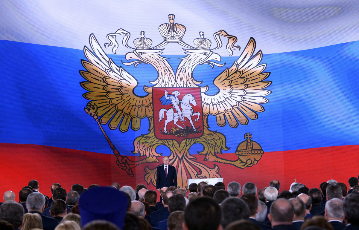 Russian President Vladimir Putin (back) stands on the stage as he addresses the Federal Assembly, including the State Duma parliamentarians, members of the Federation Council, regional governors and other high-ranking officials, in Moscow, Russia