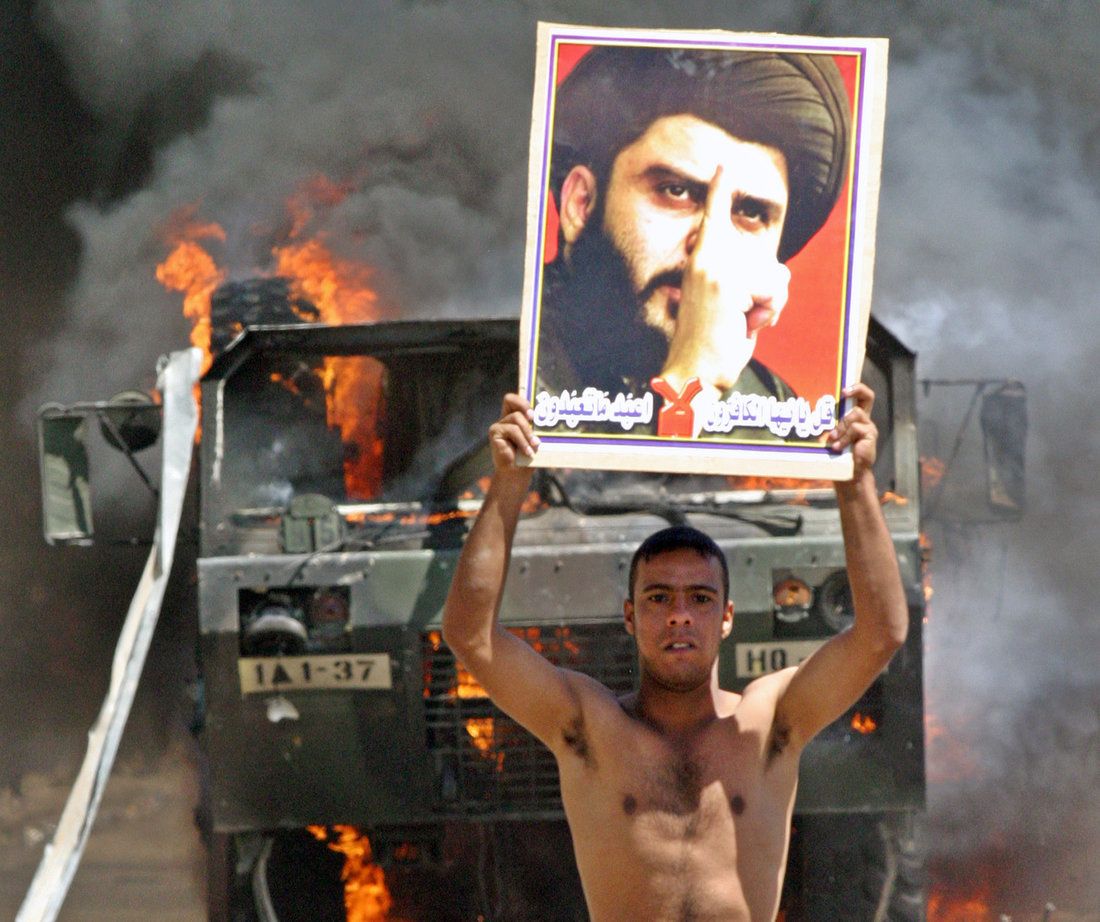 An Iraqi Shi'ite supporter of cleric Moqtada Al Sadr celebrates near a burning U.S. Army truck in the Shuala neighbourhood of Baghdad April 5, 2004. REUTERS/Ceerwan Aziz Pictures of the Year 2004 CLH/