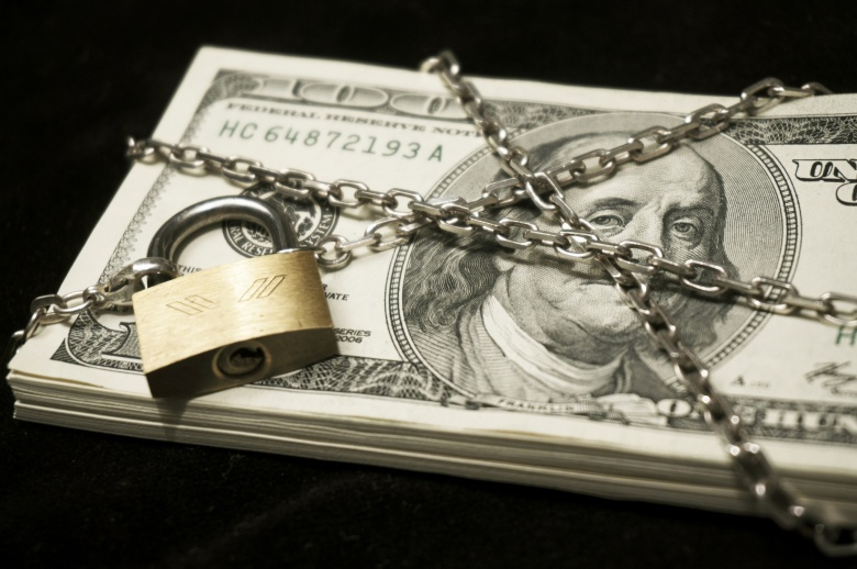 Hundred-dollar bills under lock and chain. Flickr/@Pictures of Money