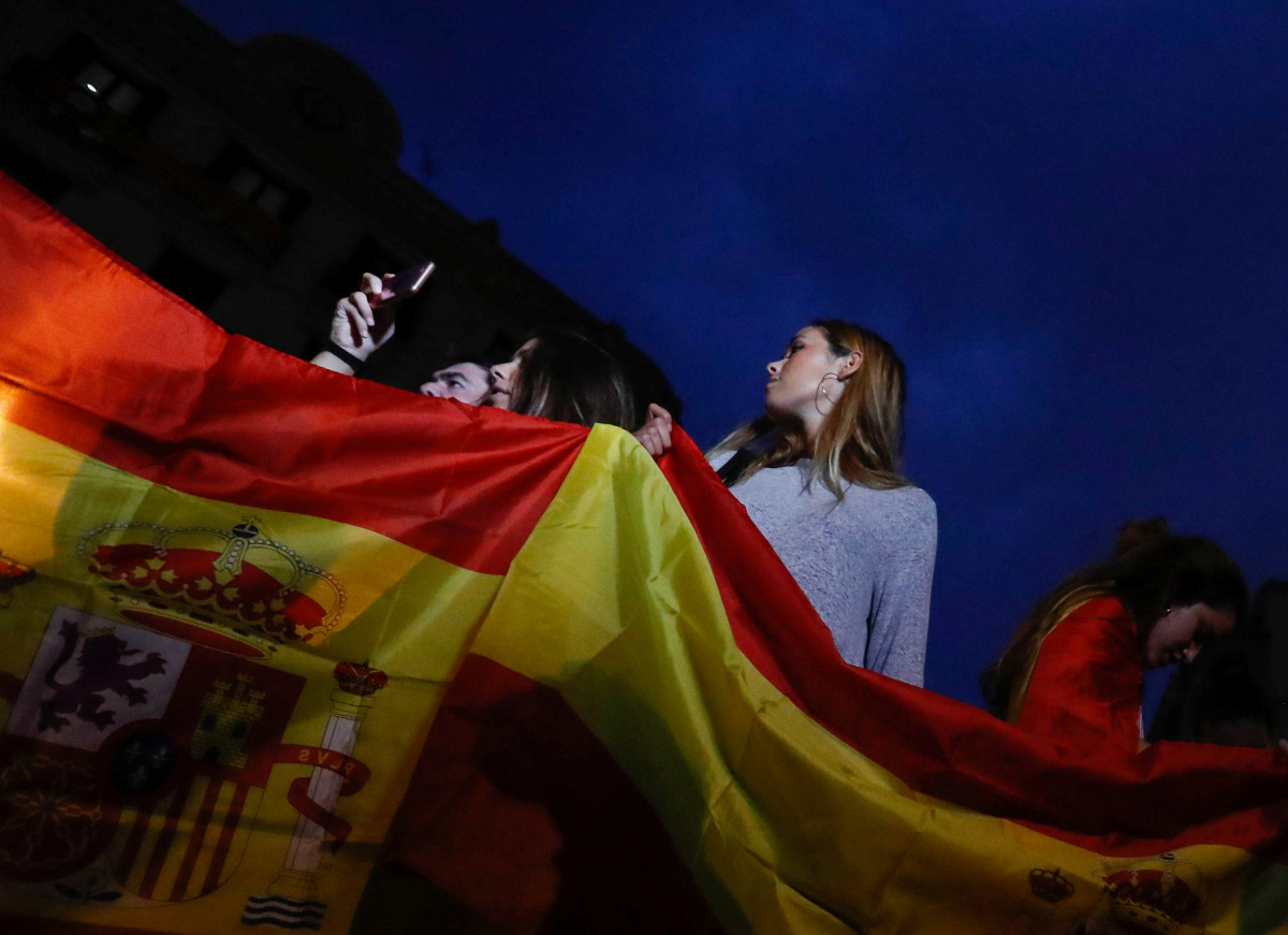 People hold Spanish flags during a gathering in favour of a unified Spain in Barcelona