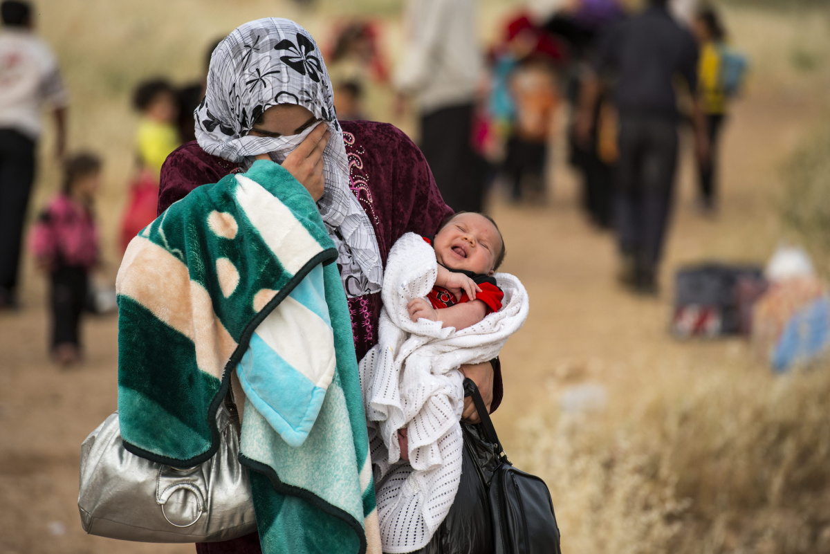 A young mother crosses the border from Syria and becomes a refugee. Flickr / UNHCR / S. Rich