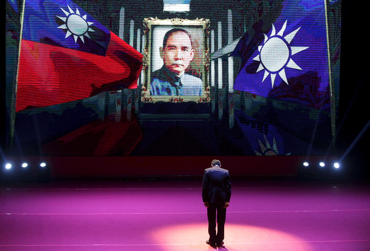 Taiwan's ruling Nationalist Kuomintang Party (KMT) chairman and presidential candidate Eric Chu bows to Taiwan's national flag, KMT's flag and a portrait of the founding father of the Republic of China, Dr. Sun Yat-sen at a party congress in Taipei