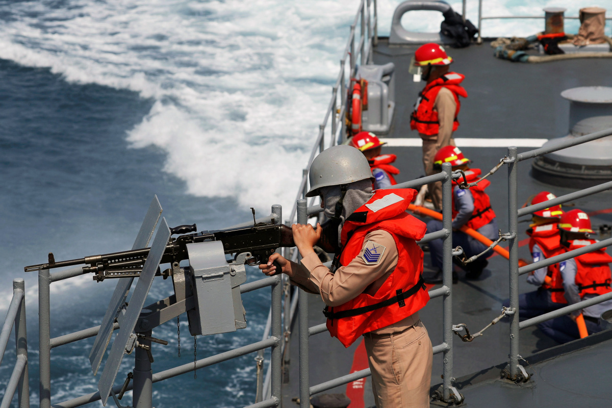A navy personnel holds a machine gun on Kee Lung (DDG-1801) destroyer during a drill, near Yilan naval base