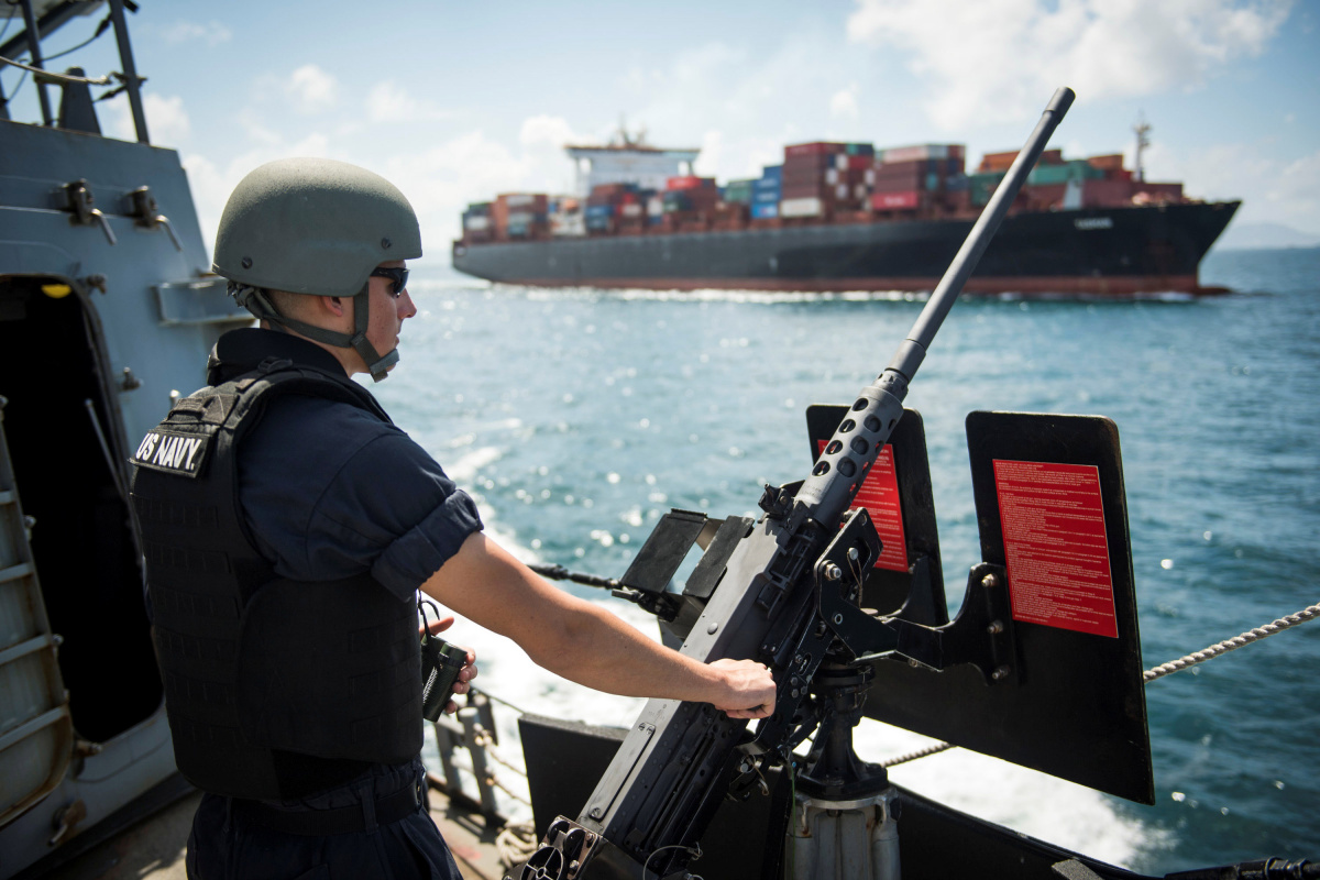 Drake Sierra assigned to the Arleigh Burke-class guided-missile destroyer USS Chafee mans a machine gun as the ship arrives in Hong Kong