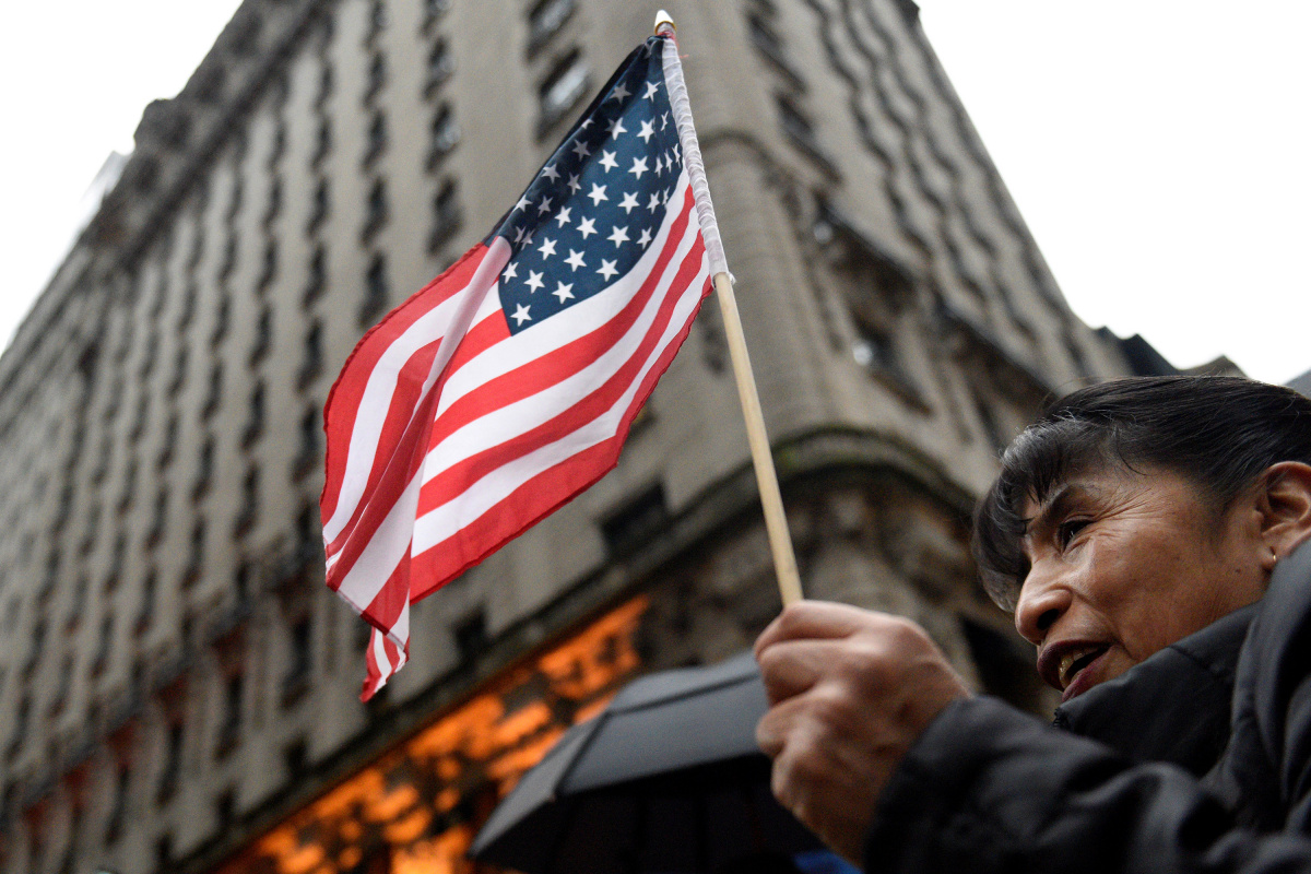A women holds an American flag while protesting outside Trump Tower during a demonstration organized by the New York Immigration Coalition against President-elect Donald Trump in the Manhattan borough of New York