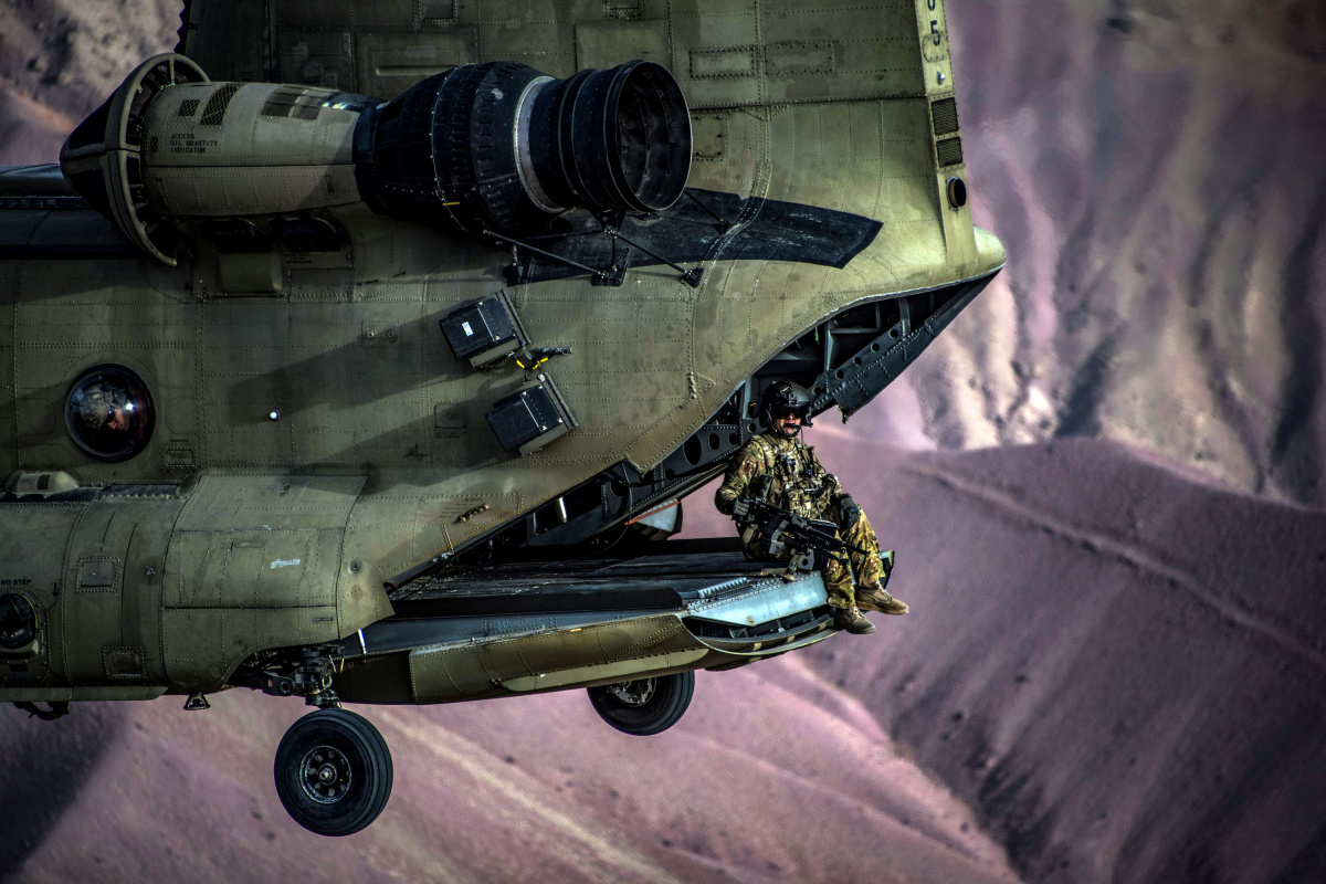 A U.S. Army CH-47F Chinook helicopter flight engineer sits on the ramp during a training exercise at Bagram Airfield
