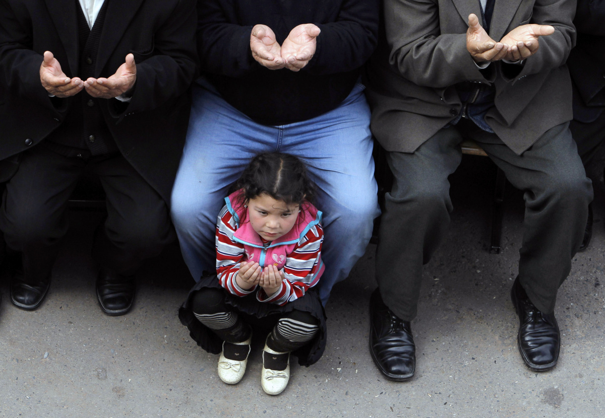 A girl prays during a rally held by ethnic Uzbeks in the town of Jalalabad in southern Kyrgyzstan