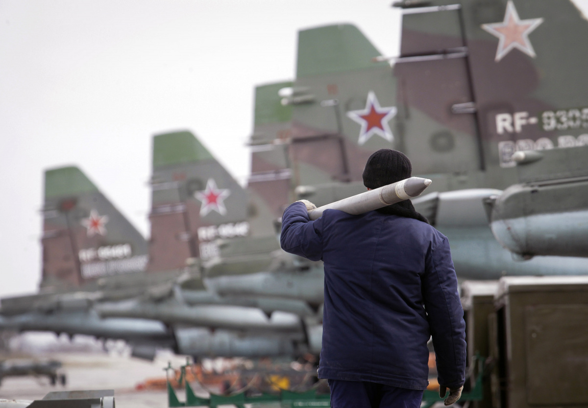 A serviceman carries a air-to-ground missile next to Sukhoi Su-25 jet fighters during a drill at the Russian southern Stavropol region