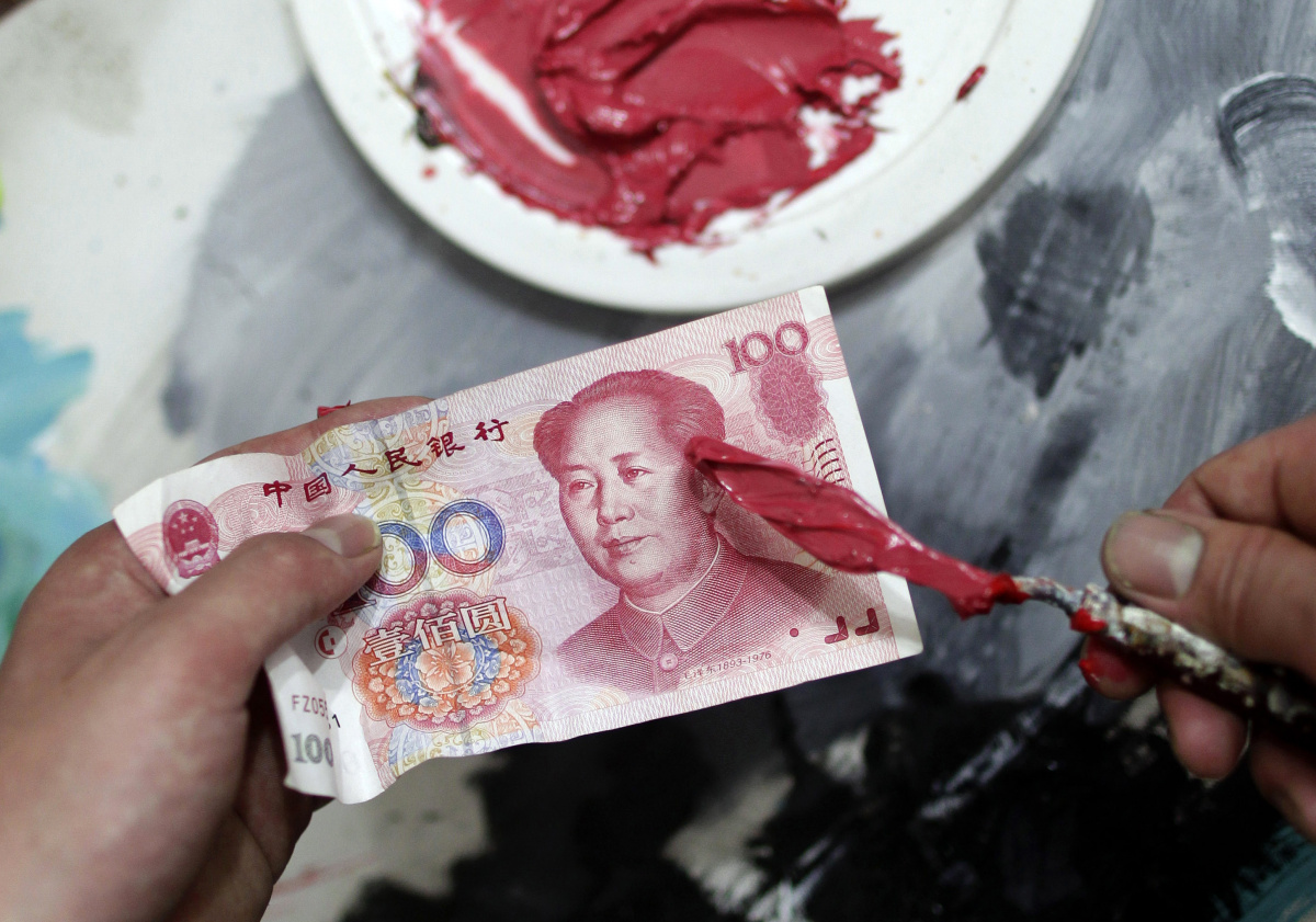 """A painter contrasts the reddish-pink hue on a painting knife with China's 100 yuan banknote before he works on portraits for Chinese artist and film-maker Zhang Bingjian's """"Hall of Fame"""" project in a studio in Shenzhen, south China's Guangdong province"""