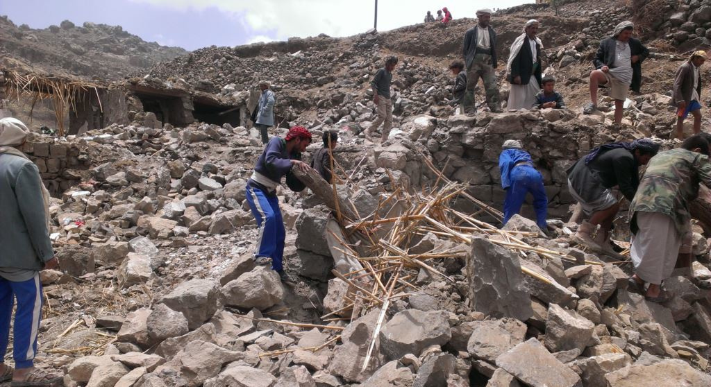 Villagers scour rubble for belongings scattered during the bombing of Hajar Aukaish, Yemen, in April 2015. Wikimedia Commons/Voice of America