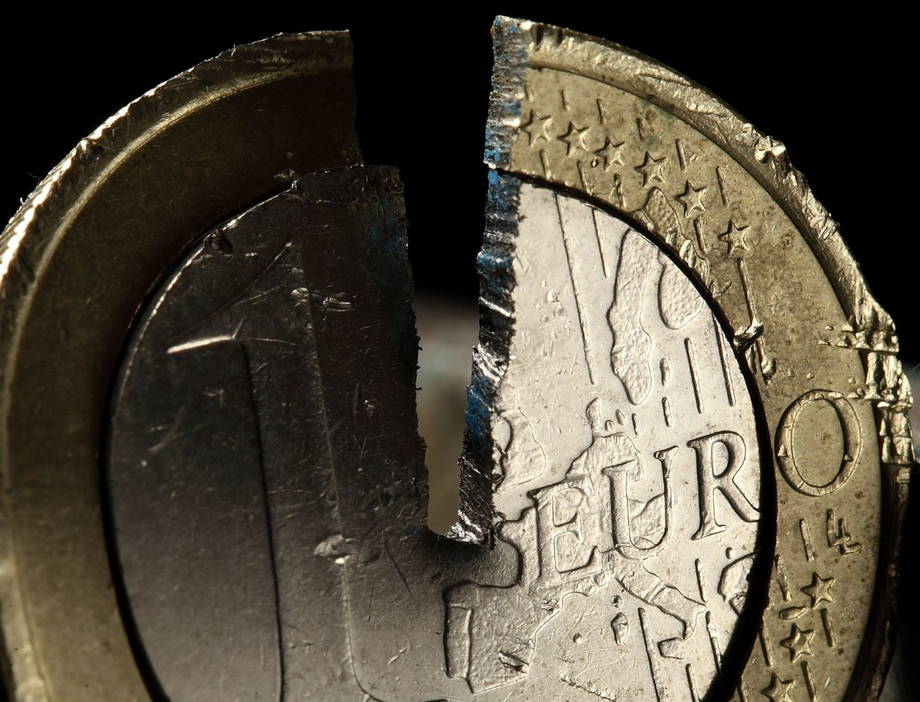 A damaged one Euro coin being held in a vise is pictured in this photo illustration taken in Warsaw September 11, 2012. Germany's Constitutional Court will determine the fate of the euro zone in a keenly-awaited ruling on September 12, 2012 that is expected to give a green light to the region's permanent new bailout fund, the European Stability Mechanism (ESM). REUTERS/Kacper Pempel (POLAND - Tags: BUSINESS TPX IMAGES OF THE DAY)