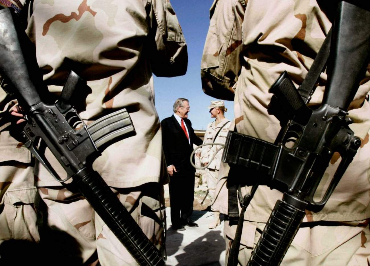Soldiers from the 173rd Airborne stand while waiting to have their picture taken with U.S. Secretary of Defense Donald Rumsfeld (C, left) before he leaves for Baghdad, in Khandahar, Afghanistan December 22, 2005. Rumsfeld said on Thursday a rapid withdrawal of U.S. forces from Iraq or Afghanistan would spawn more terrorism in the region and raise the risk of attacks on the United States. Addressing U.S. troops on the second day of a visit to Afghanistan, Rumsfeld said