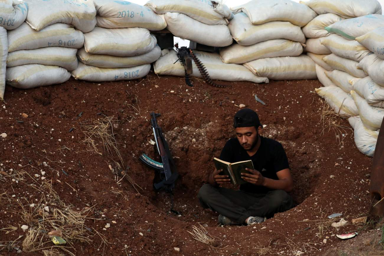 A Free Syrian Army fighter reads the Quran in the rebel-held town of Dael, Syria May 30, 2018. REUTERS/Alaa Al-Faqir