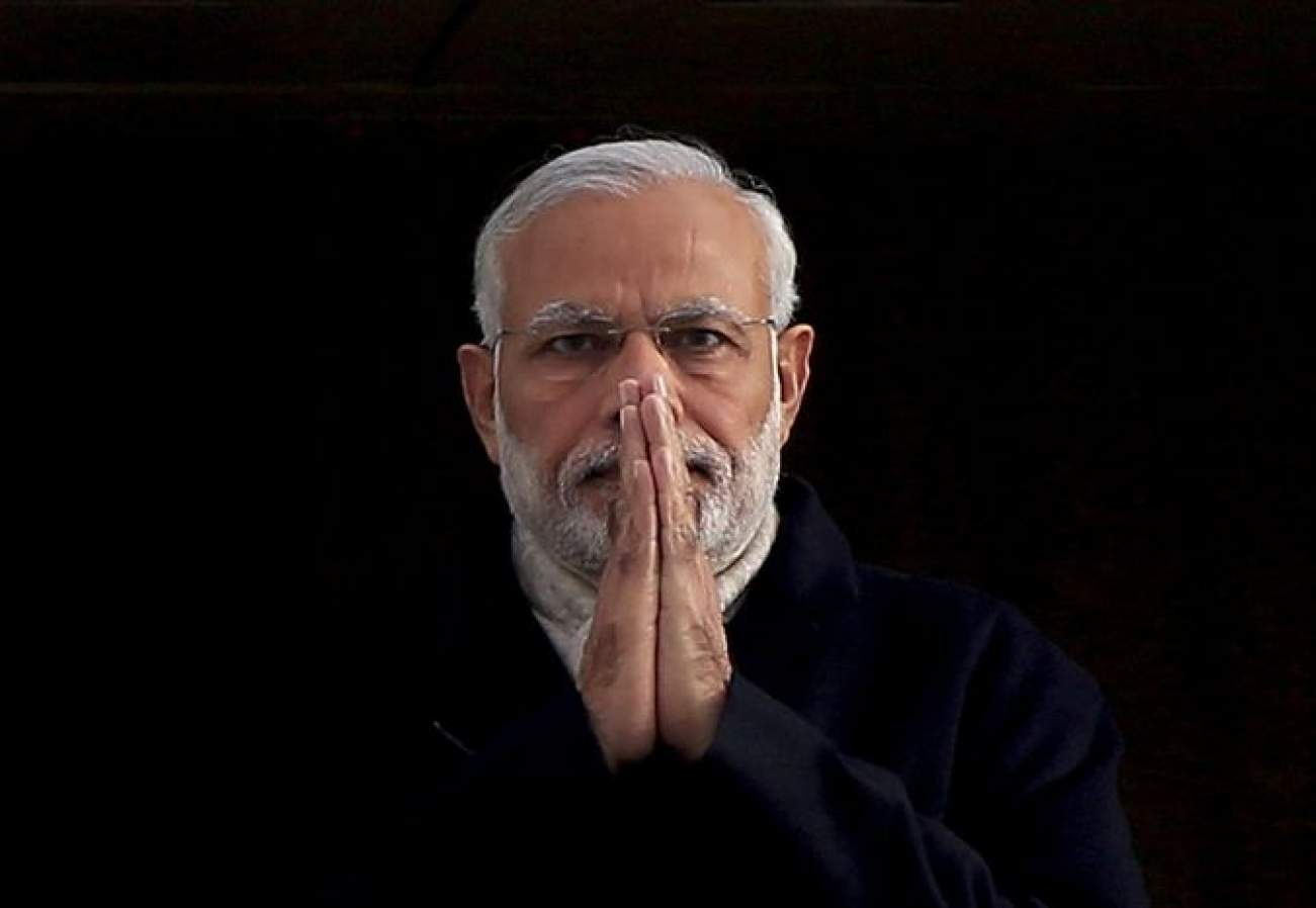 India's Prime Minister Narendra Modi holds up his hands in a