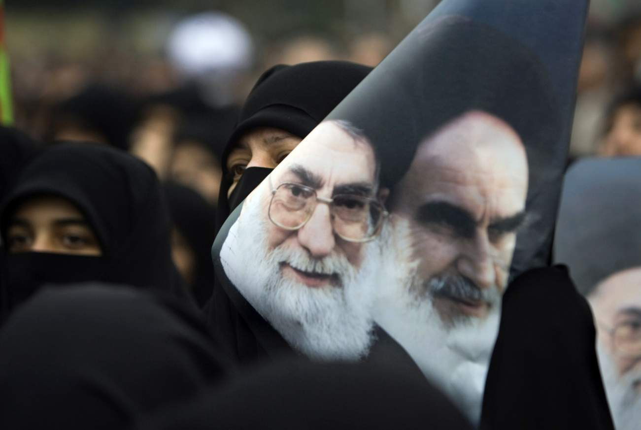 A government supporter holds a poster with images of Iran's late leader Ayatollah Ruhollah Khomeini (R) and Supreme Leader Ayatollah Ali Khamenei during a protest against opposition demonstrations during Ashura in Tehran