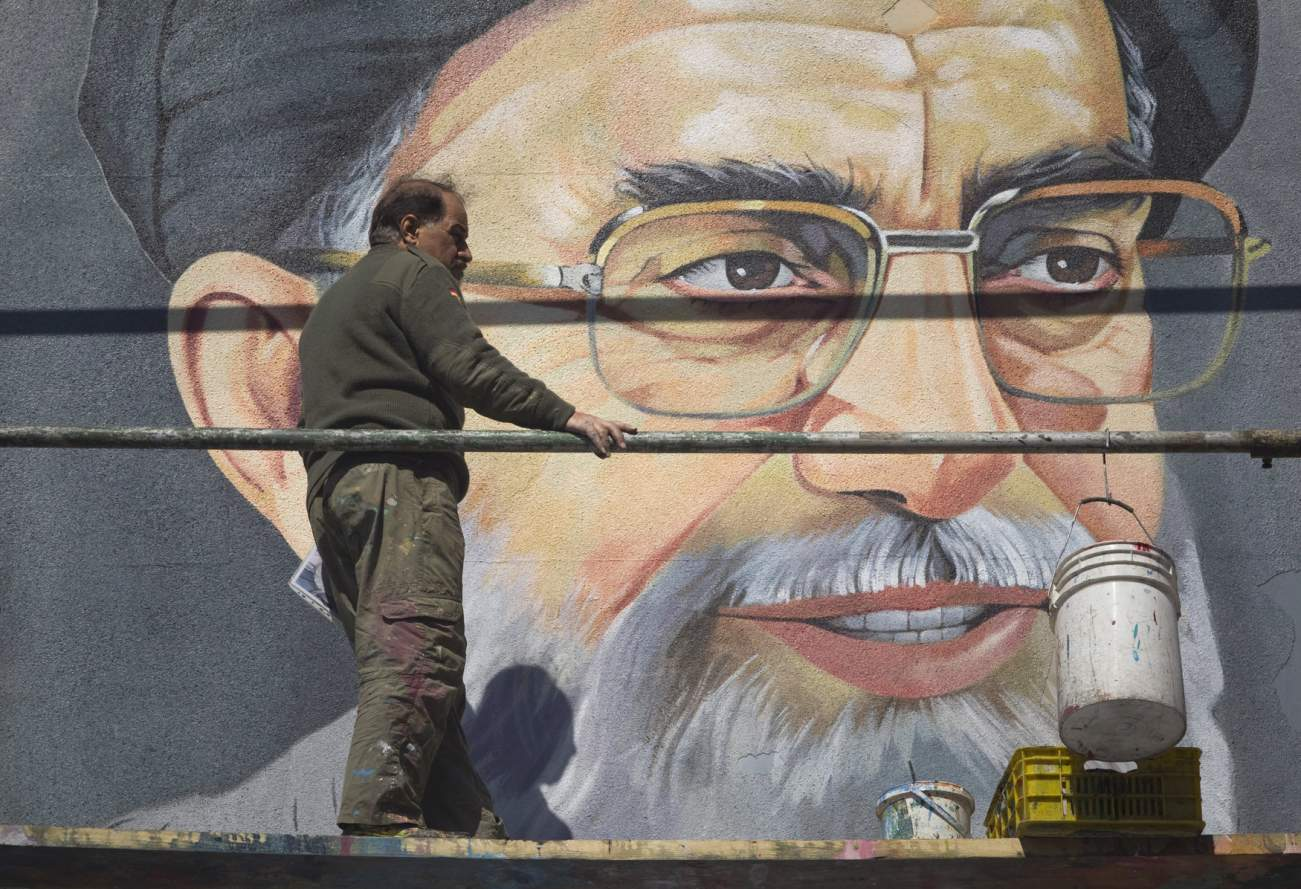 An Iranian worker rests in front of a huge portrait of Iran's Supreme Leader Ayatollah Ali Khamenei on a wall near a university during Friday prayers in Tehran February 24, 2012. REUTERS/Morteza Nikoubazl