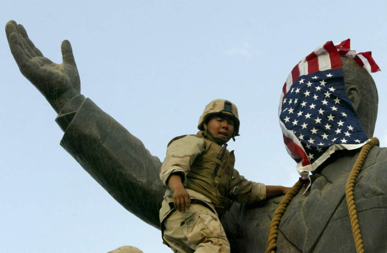 A U.S. Marine covers the face of a statue of Iraqi President Saddam Hussein with a U.S. flag in Baghdad, Iraq April 9, 2003. REUTERS/Goran Tomasevic/File Photo