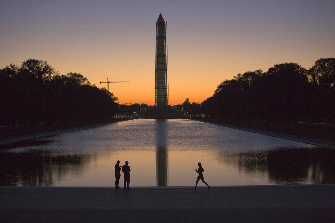 A couple (L) and a jogger pass by the Lincoln Memorial Reflecting Pool before sunrise in Washington, September 24, 2013. The nation's capital is enjoying mild temperatures during the first week of autumn.