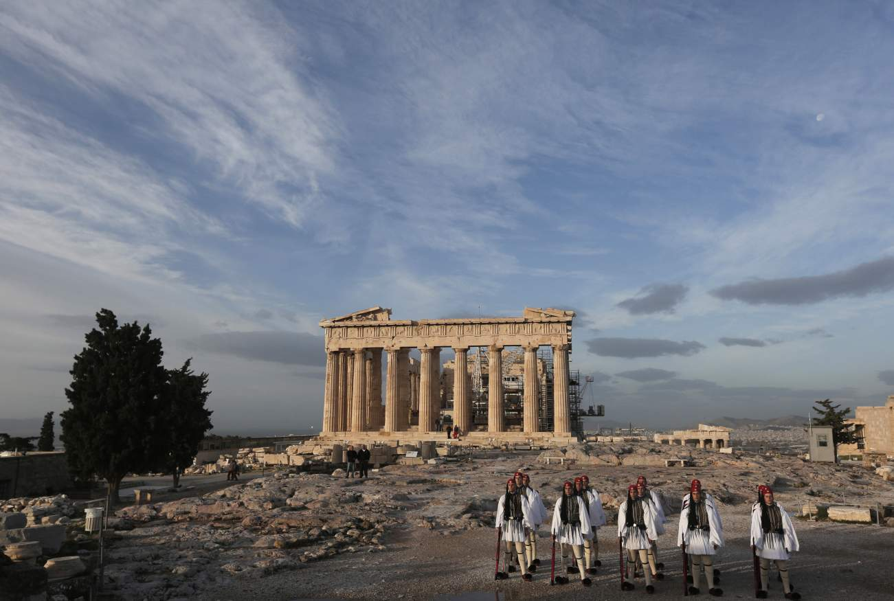 Greek Presidential Guards stand in front of the Parthenon temple during the flag hoisting ceremony at the Acropolis hill in Athens November 21, 2013. Known in Greece as Evzones, the Presidential Guards stand still outside parliament even as violent clashes break out between police and protesters, conjuring an image of stoicism in a country struggling to pull itself out of a crisis. The role of the Presidential Guard, which was founded in 1868, is purely ceremonial, but the Evzones are drawn from the Greek a