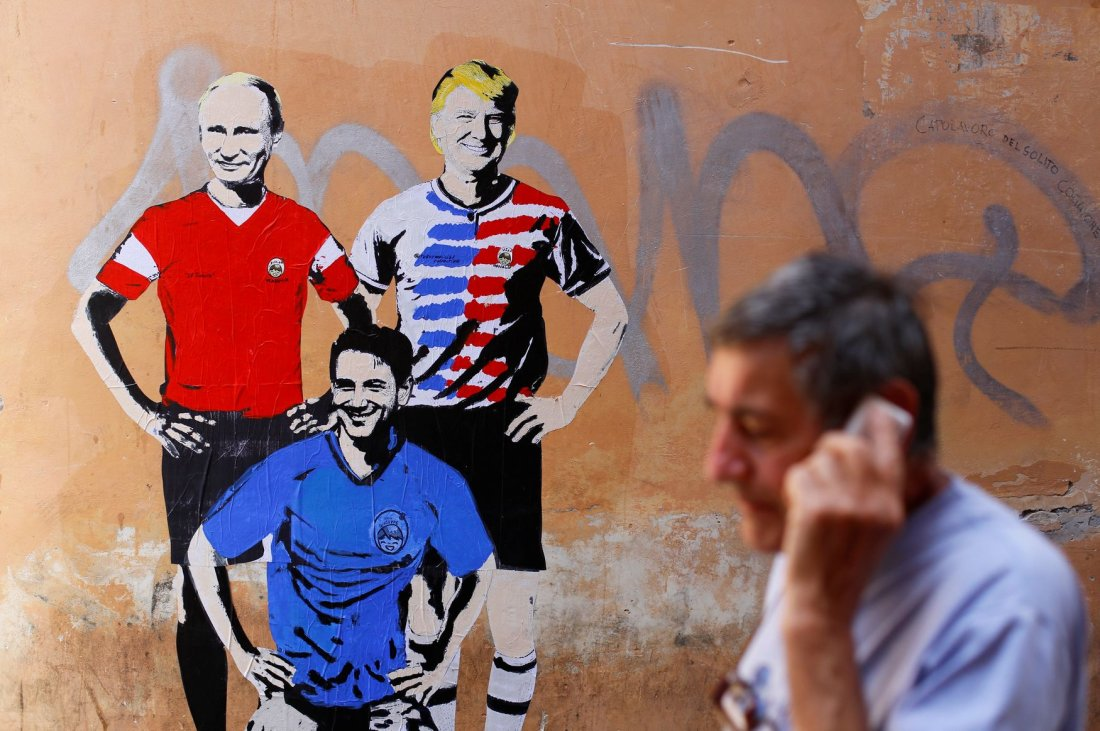 """A man walks past a mural signed by """"TV Boy"""" and depicting Russian President Vladimir Putin, U.S. President Donald Trump and Italian Prime Minister Giuseppe Conte as soccer players in downtown Rome, Italy June 15, 2018. REUTERS/Tony Gentile NO RESALES. NO"""