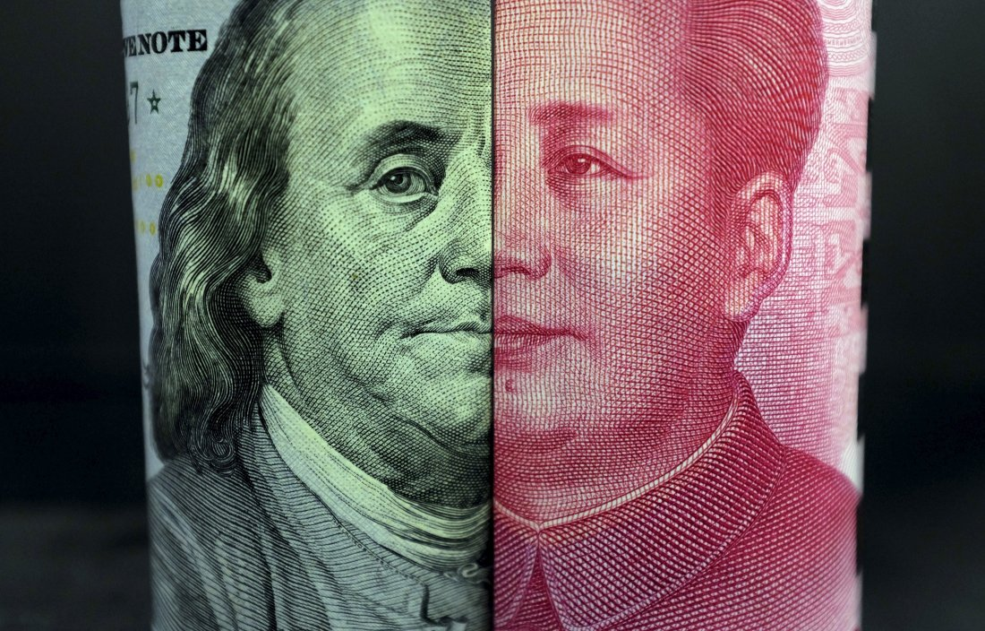 A U.S. 100-dollar banknote with a portrait of Benjamin Franklin and a Chinese 100-yuan banknote with a portrait of late Chinese Chairman Mao Zedong are seen in the picture illustration in Beijing, China, January 21, 2016.