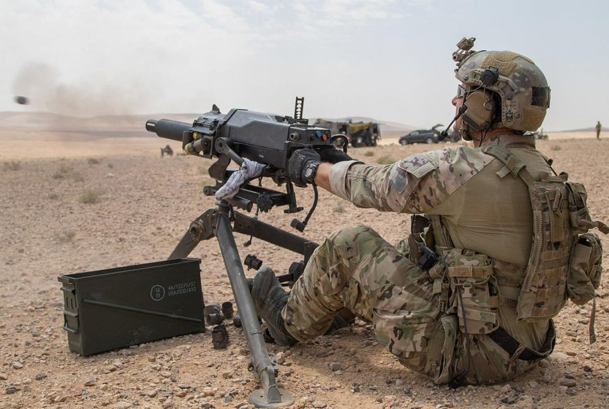 A soldier assigned to U.S. Army Special Operations Command demonstrates firing positions on the Mk 47 Strike 40mm grenade launcher to a member of the Saudi Arabian Naval Special Forces during joint forces weapons training in a tactical training area in Am
