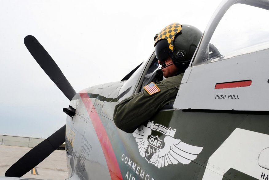 Larry Lumpkin, pilot of the P-51 Mustang, dons his helmet and flight suit for a media photo shoot at the Council Bluffs Municipal Airport, Iowa, on June 27. (U.S. Air Force photo by Josh Plueger)