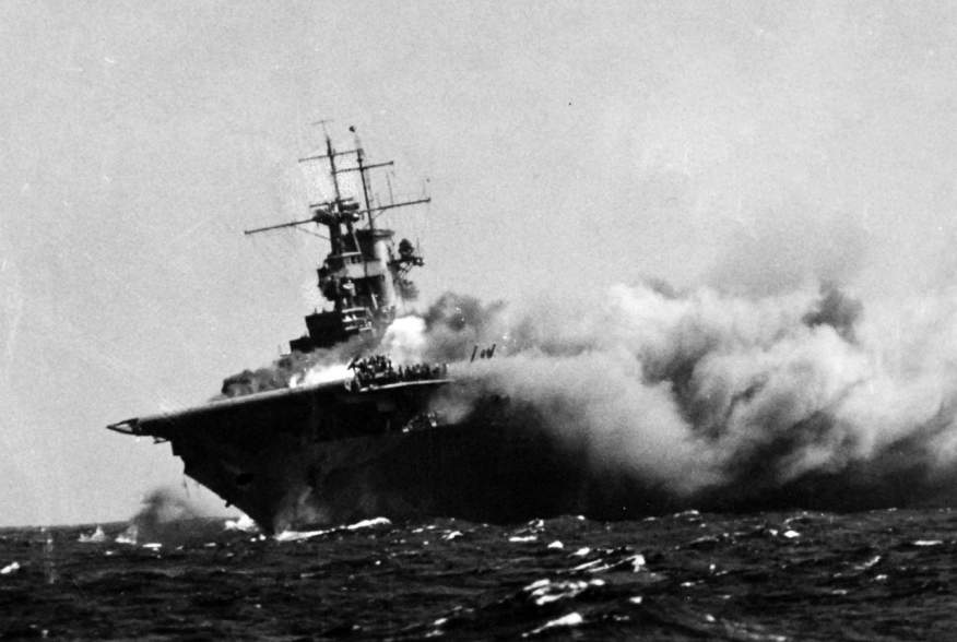 A port bow view of the ship shows her aflame and listing to starboard, 15 September 1942. Men on the flight deck desperately battle the spreading inferno.